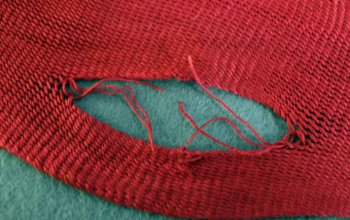 Damaged thread in a sprang sash leaves a slit.